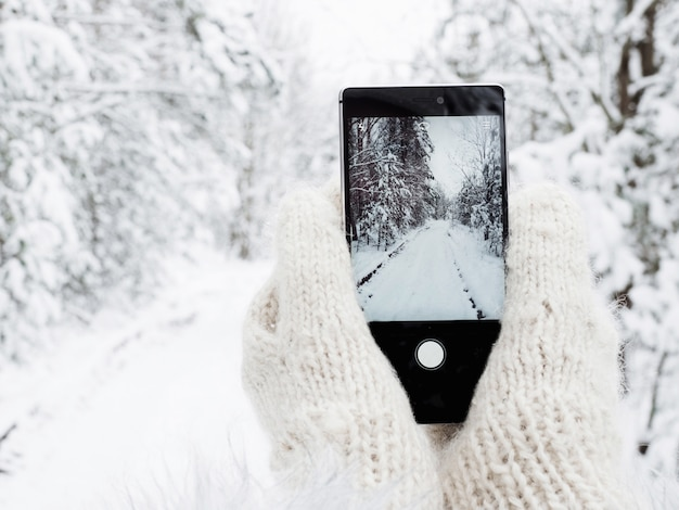 Fille tient un téléphone portable dans des mitaines en laine Photo Premium