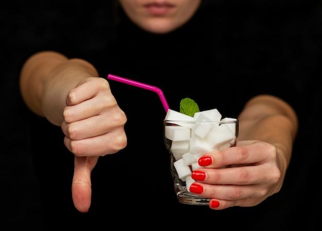 Une Fille Tient Un Verre Rempli De Cubes De Sucre Blanc Et Refuse L'utilisation Du Sucre Photo Premium