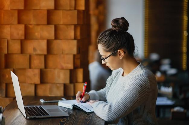 Fille travaillant sur un ordinateur portable dans un restaurant Photo Premium