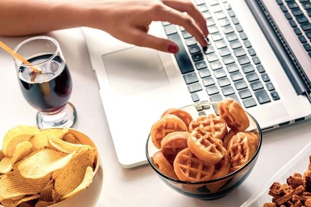 Une fille travaille devant un ordinateur et mange des fast foods Photo Premium