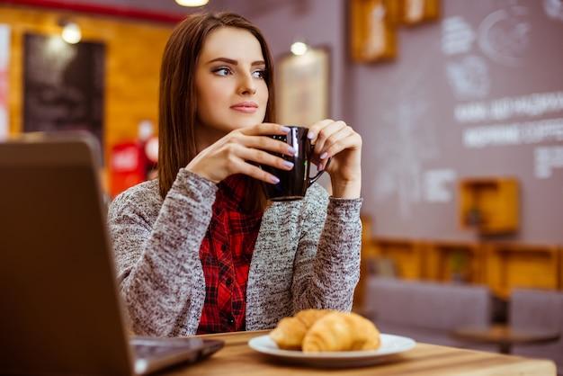 Fille travaille à un ordinateur portable et boit du thé. Photo Premium