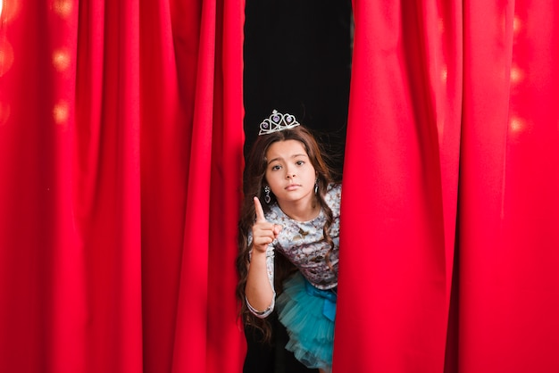 Fille triste debout derrière le rideau rouge gesticulant Photo gratuit