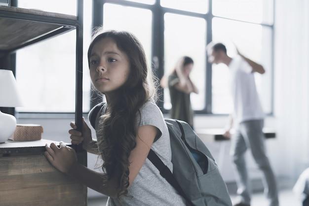 Une fille triste écoute comment les parents se battent à la maison Photo Premium