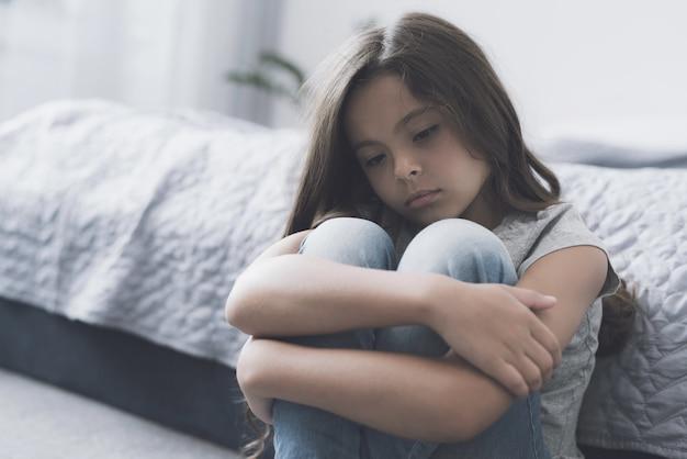 Une fille triste enveloppe ses jambes et s'assoit par terre dans la chambre Photo Premium