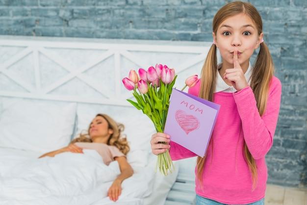 Fille avec des tulipes et carte de voeux tenant un doigt sur les lèvres Photo gratuit