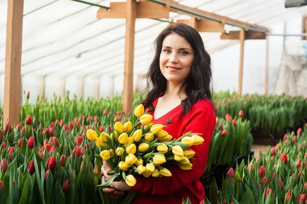 Fille avec des tulipes cultivées dans une serre. Photo Premium