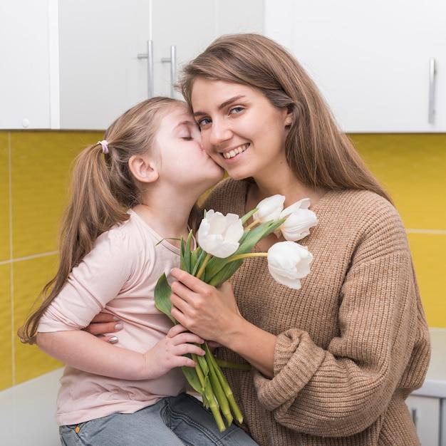 Fille avec des tulipes embrassant sa mère sur la joue Photo gratuit