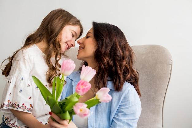 Fille avec des tulipes étreignant mère dans un fauteuil Photo gratuit