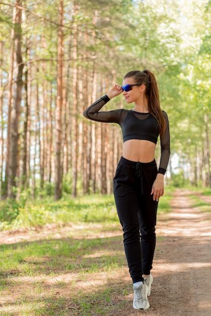 Fille en uniforme et lunettes de soleil faisant du sport dans un parc Photo Premium