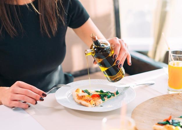 La fille verse une pizza à l'huile. Photo Premium