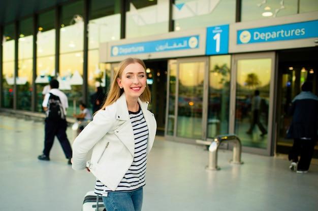 Fille en veste blanche et chemises dénudées avec valise de l'aéroport Photo gratuit