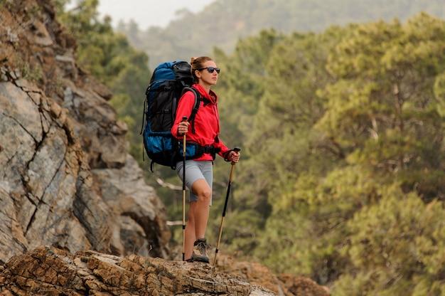 Fille en veste rouge debout sur le rocher avec sac à dos de randonnée Photo Premium