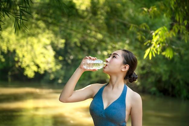 Fille en vêtements de sport eau potable Photo Premium