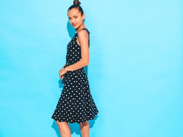 Fille Vêtue D'une Robe à Pois. Modèle Posant Près D'un Mur Bleu En Studio. Femme Positive Photo gratuit