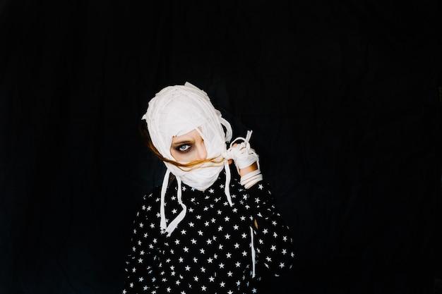 Fille avec un visage bandé sur fond noir Photo gratuit