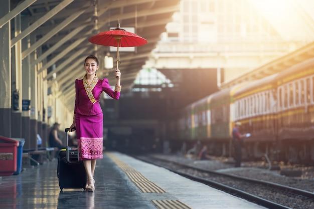 Fille de voyageur marchant et attend le train sur le quai Photo Premium