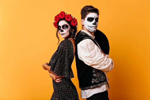 Fille Zombie Galbé En Robe Noire Posant Avec Son Petit Ami. Photo Intérieure D'un Beau Couple Avec Un Maquillage De Crâne. Photo gratuit