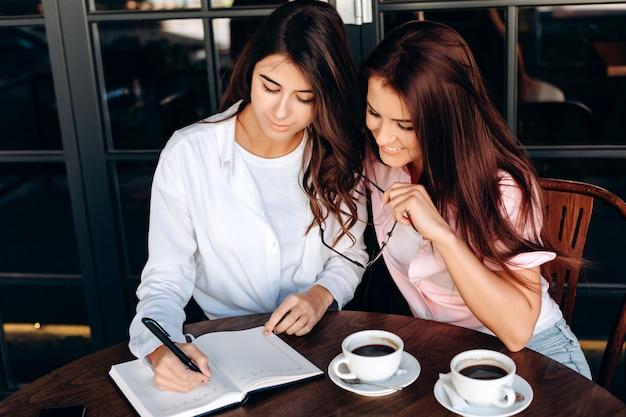 Filles d'affaires travaillant dans un café, écrivant quelque chose d'important dans le bloc-notes Photo Premium