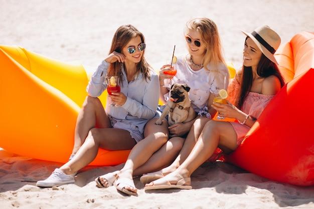Filles amis avec des cocktails assis sur un matelas de piscine Photo gratuit