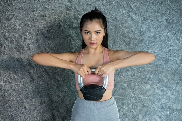 Des filles asiatiques font de l'exercice avec la kettlebell dans la salle de sport. Photo gratuit