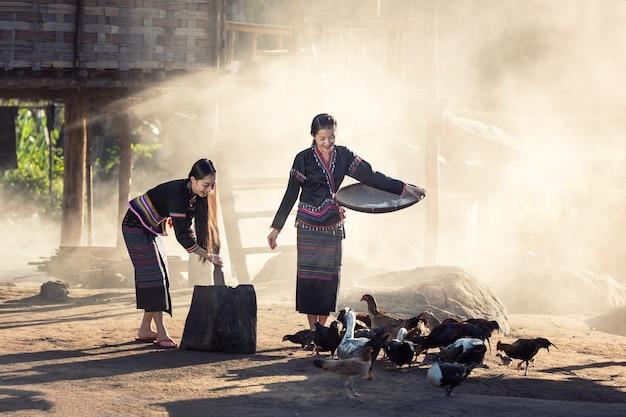 Filles Asiatiques (hmong) Nourrissant Des Poulets Dans La Campagne Laotienne Photo Premium