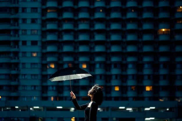 Filles asiatiques en noir tiennent un parapluie rougeoyant levant les yeux vers le ciel la nuit dans une ville avec des lumières. Photo Premium