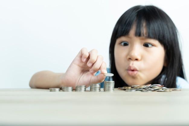 Les Filles Asiatiques Sont Heureuses D'organiser Des Pièces Et De Compter Les Pièces Pour économiser De L'argent Avec Le Mur Blanc. Photo Premium