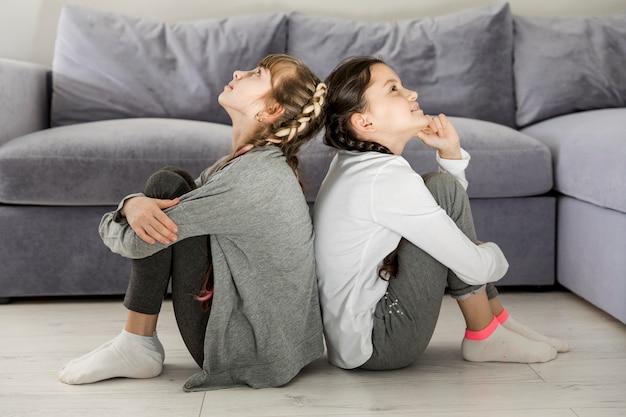 Filles assis dos à dos Photo gratuit