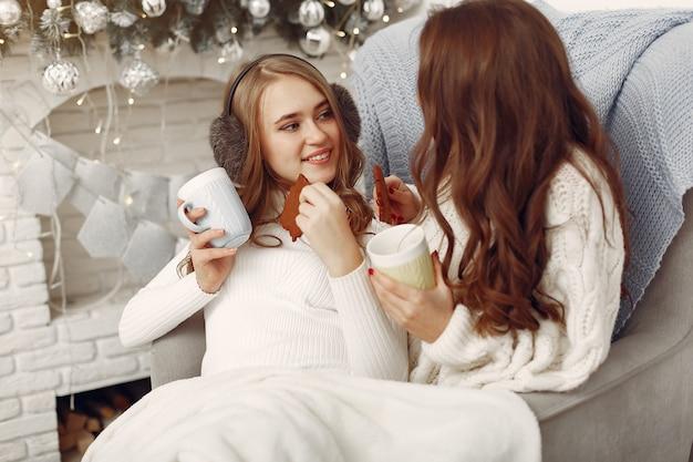 Filles Assises Sur La Chaise. Femmes Avec Des Tasses. Sœurs Se Préparent Pour Noël Photo gratuit