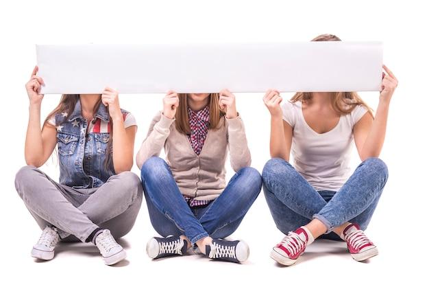 Des Filles Assises En Jambes Et Fermées Font Face à Une Table Blanche. Photo Premium