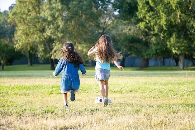 Filles Aux Cheveux Noirs Actifs En Cours D'exécution Pour Un Ballon De Football Sur L'herbe Dans Le Parc De La Ville. Pleine Longueur, Vue Arrière. Concept D'activité D'enfance Et De Plein Air Photo gratuit