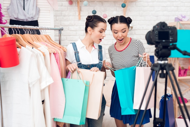 Des filles bloggeuses présentent de nombreux sacs colorés à la caméra Photo Premium