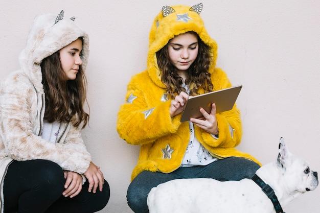 Filles avec un chien en regardant une tablette Photo gratuit