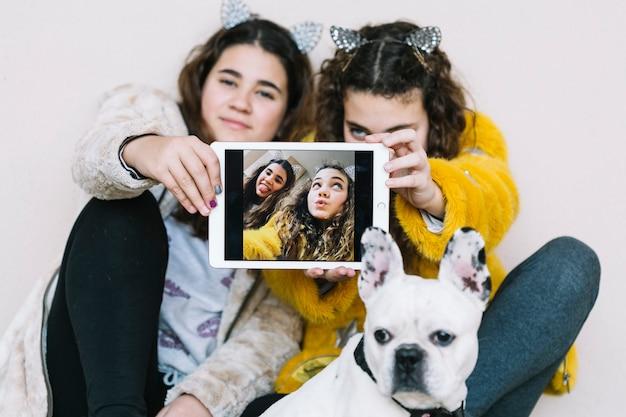 Filles avec un chien et une tablette Photo gratuit