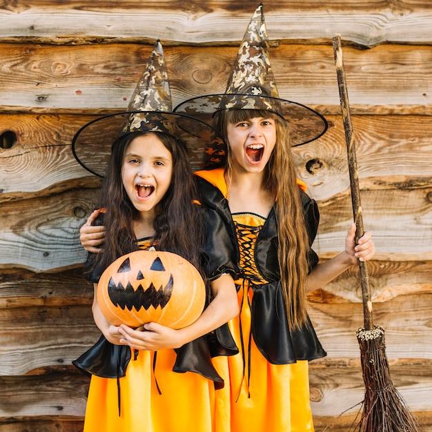 Filles en costumes de sorcière faisant des grimaces tenant un balai et une citrouille Photo gratuit