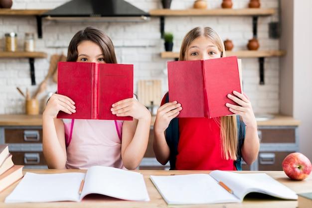 Filles couvrant des visages avec des livres Photo gratuit
