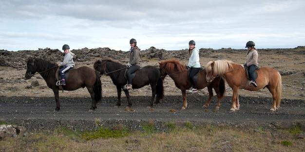 Filles dans des casques d'affilée sur des chevaux islandais Photo Premium