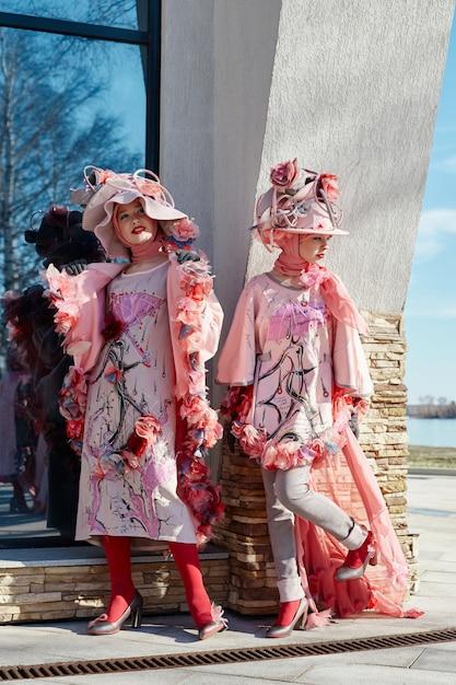 Filles Dans De Nouveaux Vêtements Créatifs De Mode Vogue Posant Dans La Rue, Robe Rose Et Chapeau, Vêtements Ethniques Photo Premium