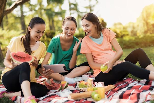 Filles dans sportswear. femmes enceintes regarder la tablette. Photo Premium