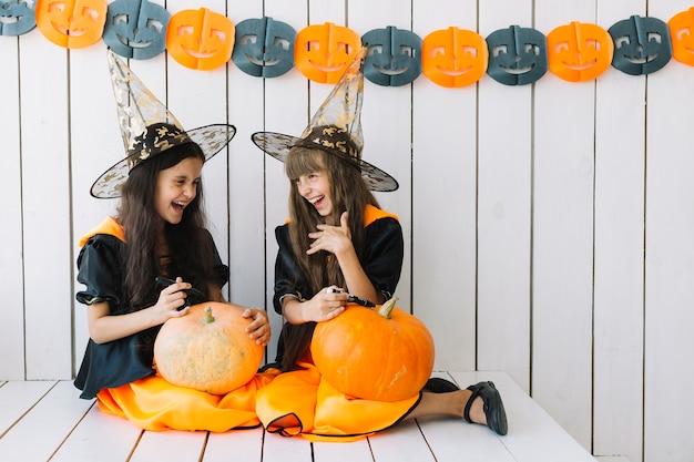Filles décorant des citrouilles d'halloween et riant Photo gratuit