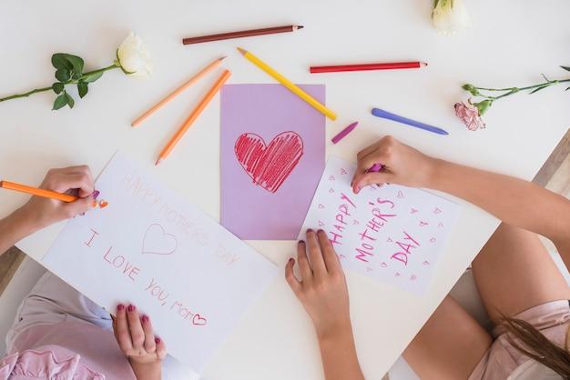 Filles dessinant des cartes de voeux pour la fête des mères Photo gratuit