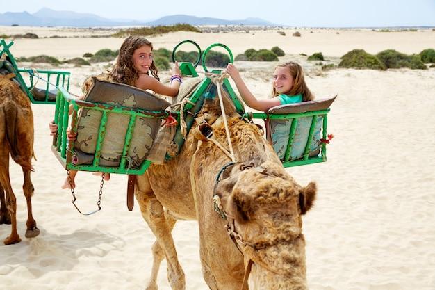 Filles à dos de chameau dans les îles canaries Photo Premium