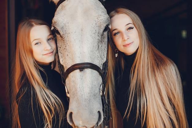 Filles élégantes avec un cheval dans un ranch Photo gratuit