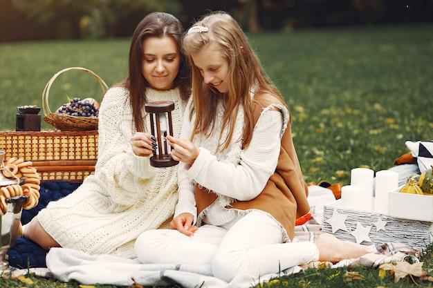 Filles élégantes et élégantes, assis dans un parc en automne Photo gratuit