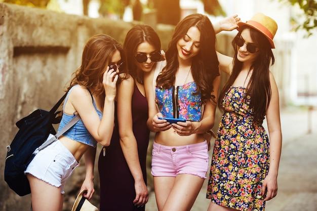 Les filles en été à la recherche d'une des photos dans un smartphone Photo gratuit