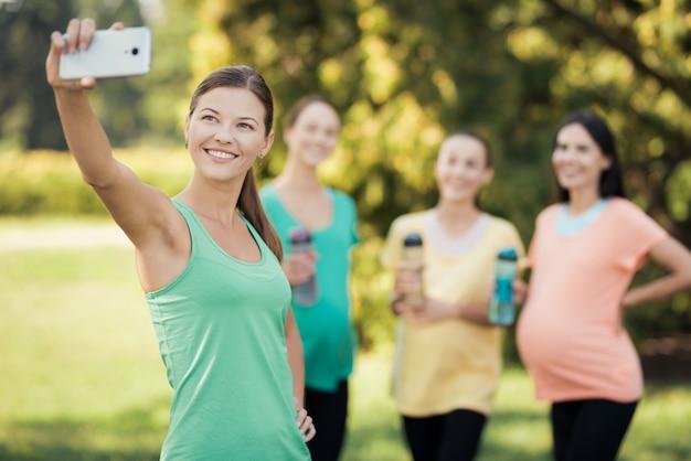 Les filles font selfie avec sourire enceinte sur smartphone. Photo Premium