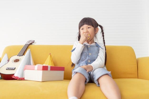 Des filles gaies et jolies pour les enfants mangent une pomme près du cadeau présent dans le salon blanc. Photo Premium