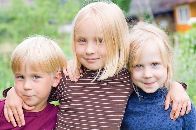 Filles Et Garçon Posant à L'extérieur Photo Premium