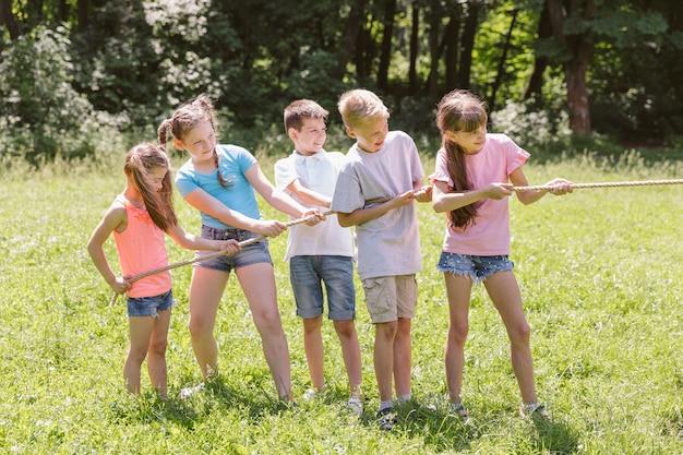Filles et garçons jouant au tir à la corde Photo gratuit