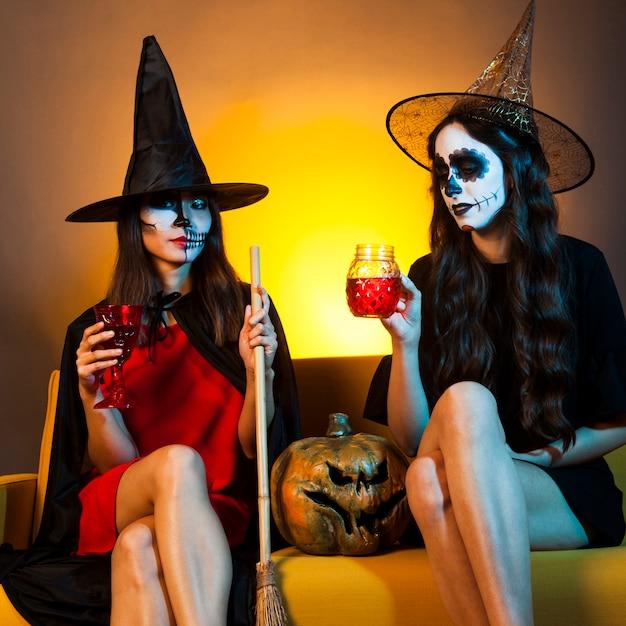 Les filles d'halloween au canapé avec de la citrouille et des boissons Photo gratuit